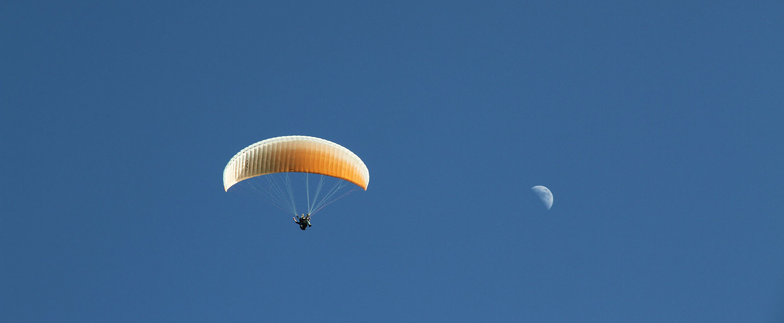 tandem paragliding with blue sky and