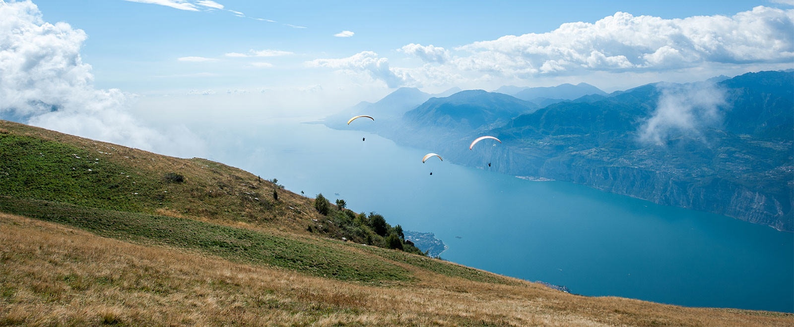 group of paragliders over lake garda